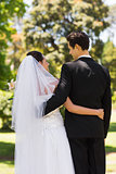 Rear view of newlywed with arms around in park