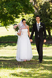 Newlywed couple holding hands and walking in park