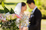 Bouquet with blurred newlywed couple in background at park