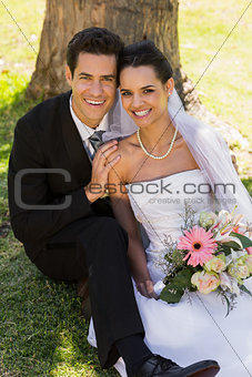Newlywed couple sitting against tree trunk in park