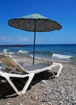 Chaise lounge under an umbrella on the beach