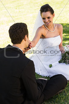 Groom kissing his beautiful bride's hand at park