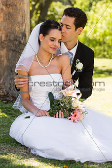 Groom kissing his beautiful bride at park