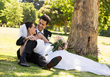 Happy newlywed couple relaxing in park