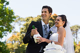 Newlywed couple with champagne bottle at park