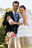 Happy newlywed with champagne bottle at park