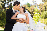 Newlywed kissing besides wedding cake at park