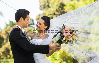 Romantic newlywed couple dancing in park