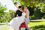 Newlywed couple sitting on scooter in park