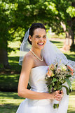 Smiling beautiful bride with bouquet standing in park