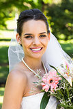 Close-up portrait of a beautiful bride with bouquet in park