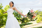 Cheerful young beautiful bride with bouquet in park