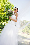 Happy young beautiful bride with bouquet in park