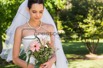 Serious beautiful bride with bouquet in park
