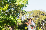 Cheerful bride throwing bouquet in park