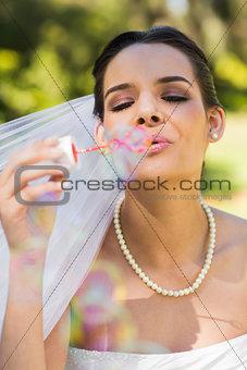 Beautiful bride blowing soap bubbles in park