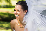 Cheerful young beautiful bride in park