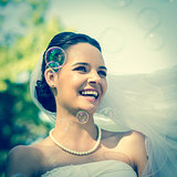 Close-up of beautiful bride looking at soap bubbles