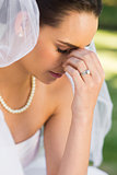 Beautiful worried bride at park