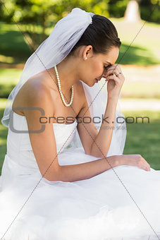 Beautiful worried bride sitting at park