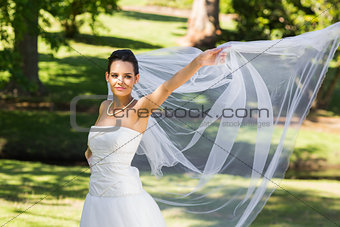 Smiling beautiful bride standing in park
