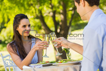 Couple toasting champagne flutes at an outdoor café