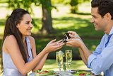 Man propose woman while they have romantic date at an outdoor café