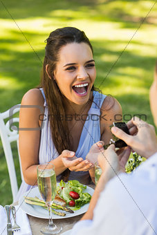 Man proposing cheerful woman at an outdoor café