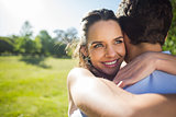 Close-up of a loving woman embracing man at park