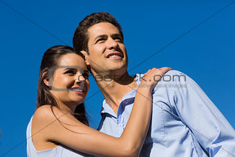 Young couple looking away against blue sky