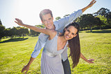 Happy couple with arms outstretched at park
