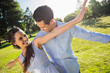 Happy young couple with arms outstretched at park