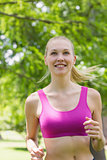Healthy and beautiful woman in sports bra jogging in park