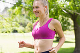 Healthy and beautiful young woman in sports bra jogging in park