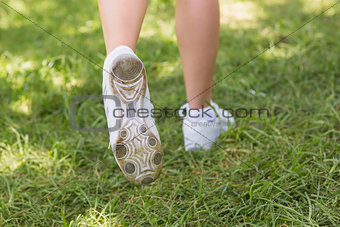 Low section of woman in sports shoes jogging at park
