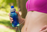 Mid section of healthy woman in sports bra with water bottle in park
