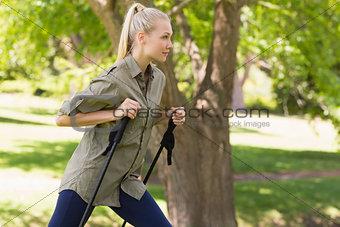 Beautiful young woman Nordic walking in park