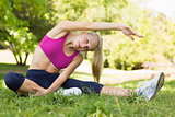Healthy and beautiful woman doing stretching exercise in park