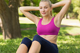 Healthy and beautiful woman doing stomach crunches in park