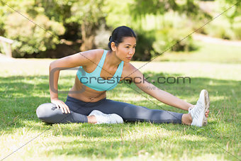 Healthy and beautiful woman stretching hand to leg in park