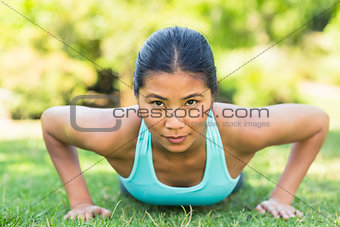 Portrait of a healthy woman doing push ups in park