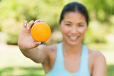 Healthy woman holding orange in park
