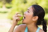 Healthy young woman eating apple in park