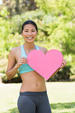 Smiling woman holding heart shape board in park