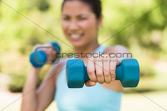 Blurred woman exercising with dumbbells in park