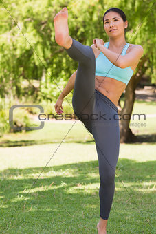 Healthy woman performing air kick in park