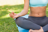 Close-up of a sporty woman in lotus pose at park