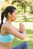 Sporty woman in Namaste position with eyes closed at park
