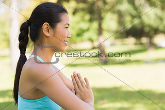 Sporty woman in Namaste position at park
