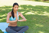Woman in Namaste position with eyes closed at park